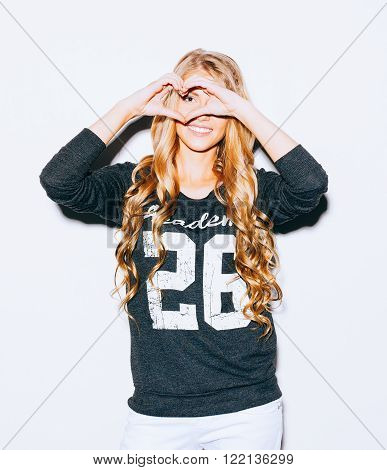 Love. Portrait smiling happy young woman with long blond hair, making heart sign, symbol with hands white wall background. Positive human emotion expression feeling life perception attitude body language. Indoor. Warm color. Hipster.