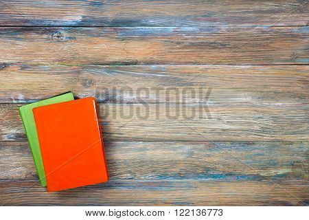 Composition with vintage old hardback books, diary, fanned pages on wooden deck table and green background. Books stacking. Back to school. Copy Space. Education background