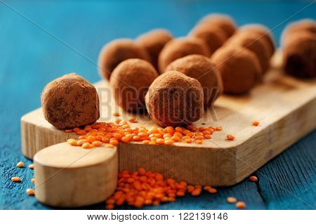 Homemade yummy lentil sweets in cocoa powder on wooden board with orange lentils