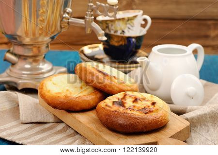 Vatrushka Russian pastry with cottage cheese served with samovar and tea horizontal