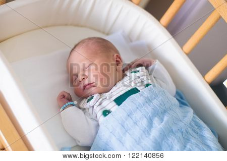 Newborn baby in hospital room. New born child in wooden co-sleeper crib. Infant sleeping in bedside bassinet. Safe co-sleeping in a bed side cot. Little boy taking a nap under knitted blanket.
