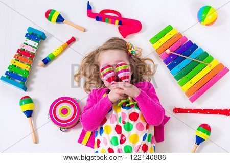 Child with music instruments. Musical education for kids. Colorful wooden art toys for kids. Little girl playing music. Kid with xylophone guitar flute.