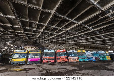 Colored buses in abandoned bus depot with scary roof