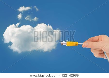 Hand holding computer cabel with cloud in sky, technology concept