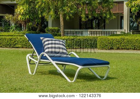 White rattan sun lounger with blue cushion and pillow in the garden