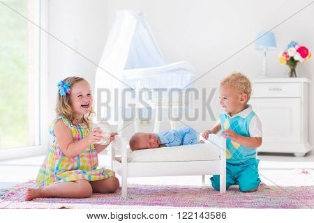 Cute little boy and girl kissing newborn brother. Toddler kids meet new born sibling at home. Infant sleeping in toy bed in white nursery. Kids playing and bonding. Children with small age difference.