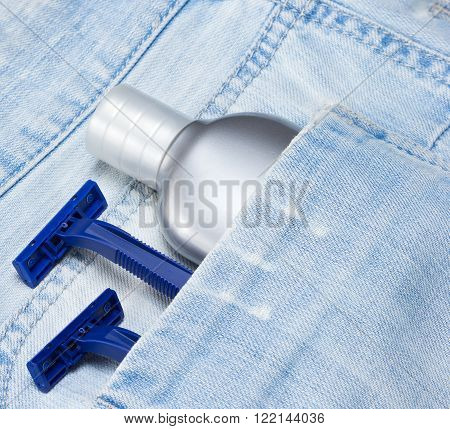 Aftershave lotion and disposable razors in shabby blue jeans pocket. Shaving cosmetic products and accessories for men. Travel kit of toiletries and cosmetics