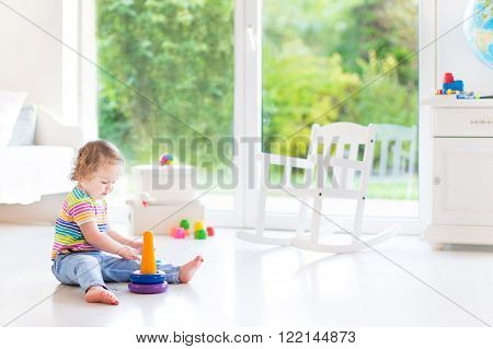 Adorable little toddler girl in a colorful shirt playing with a toy pyramid and construction blocks sitting on the floor in a white sunny bedroom with big garden view windows