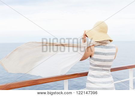 back view of young woman at cruise ship in sunhat and with waving at the wind scarf