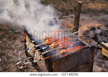 Outdoor Cooking. Tasty Sausages Grilled On A Brazier