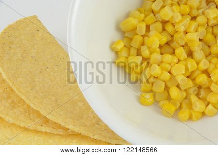 Corn tortilla taco shells and canned corn in white bowl