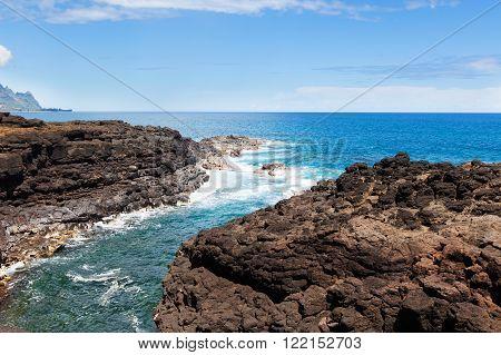 view at rocky seashore at queen's bath at kauai island hawaii