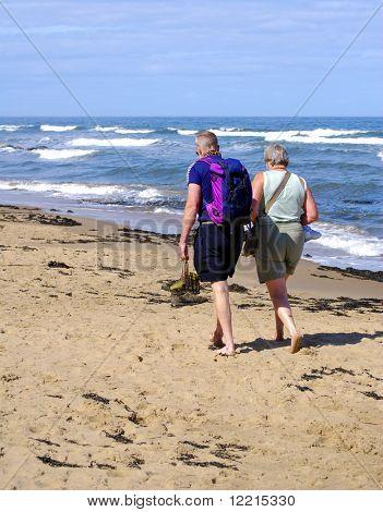 Elderly couple walking on sandy beach on sunny day