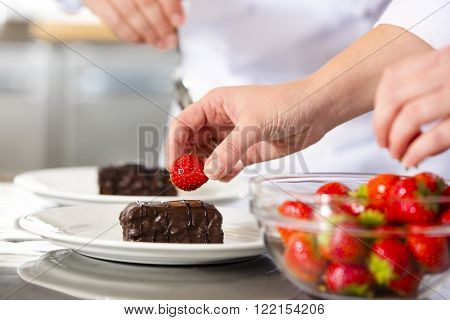 Close-up of professional chef who decorates dessert cake with strawberry and chocolate sauce. Large industry kitchen.