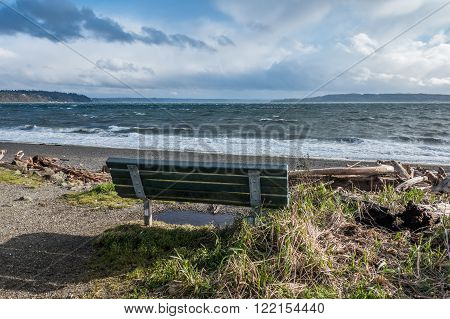 A view of the Puget Sound on a windy day. Bench in the foreground.