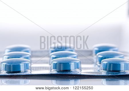 Blue medicine pills on white background. Pharmaceutical medicament. Antibiotic painkiller or narcotic closeup.