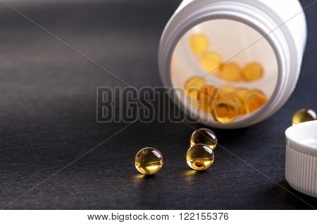 Omega capsules spilling out of a bottle. Focus on capsules.