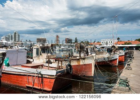 MALDONADO FEBRUARY 29 2016 - Classic Red Fishing Boats moored in front of the yachts of the rich people in Punta del Este harbor Uruguay