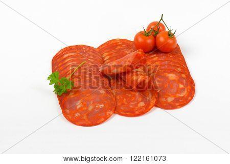 slices of chorizo salami and cherry tomatoes on white background