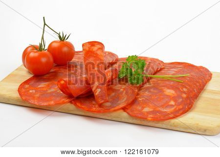 slices of chorizo salami and cherry tomatoes on wooden cutting board - close up