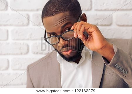 Portrait of handsome Afro American man in classic suit and glasses looking at camera against white brick wall