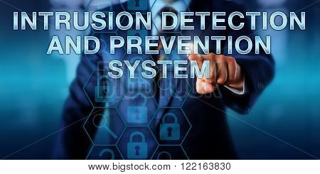 Computer security specialist is pushing INTRUSION DETECTION AND PREVENTION SYSTEM on a touch screen interface. Business metaphor and information technology concept. Copy space over office background.