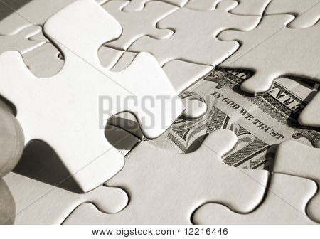 Fingers holding jigsaw piece revealing US Dollar (sepia)