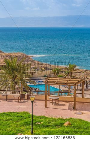 Madaba, Jordan - October 27, 2015: Hotel swimming pool on the shores of the Dead Sea in Jordan. In pure sea water visible salt crystals. On the other side of the visible area of Israel.