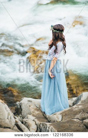 the bride looks to the moan of the stream of the mountain river standing on a rock