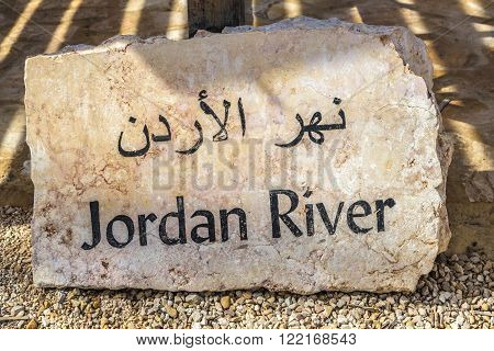 Jordan River in Bethany pointer, before going to the bank of the Jordan River. Arabic script on the granite slab.