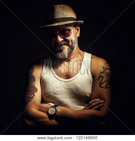 Portrait of an older man showing his tattoo.