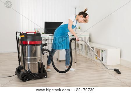 Tired Young Female Janitor Cleaning Floor With Vacuum Cleaner