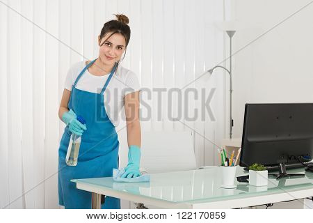 Young Female Janitor Using Spray To Wipe Desk