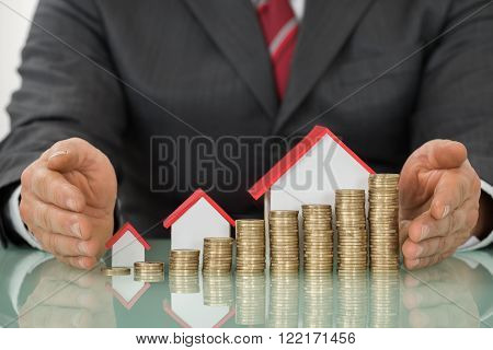 Businessman With Different Houses And Stacks Of Coins