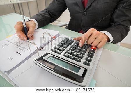 Close-up Of Businessman Calculating Invoice Using Calculator