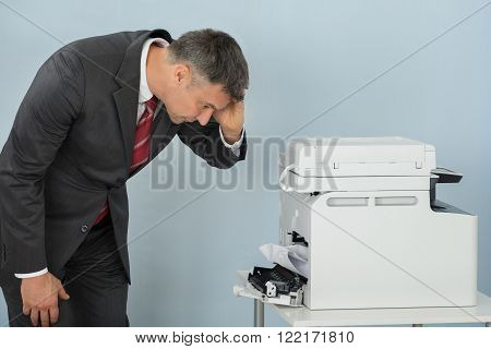 Businessman Looking At Printer Machine At Office