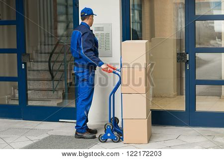 Delivery Man With Trolley Using Security To Enter Building