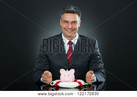 Mature Businessman Protecting Piggybank With Lifebelt