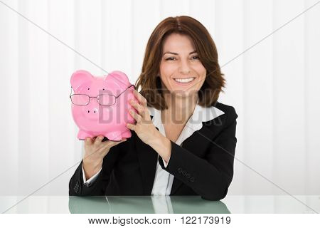Happy Young Businesswoman Holding Piggybank With Glasses