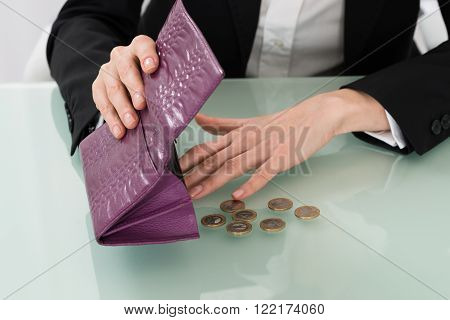 Close-up Of Businesswoman Holding Empty Purse With Euro Coins At Desk