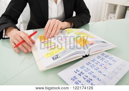 Close-up Of Businesswoman With Calendar Writing Schedule In Diary