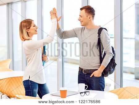 High five. Pleasant student standing near window and welcoming each other while giving five