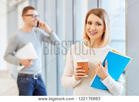 Modern  youth. Positive girl holding coffee and standing near window while student talking on the mobile phone in the background
