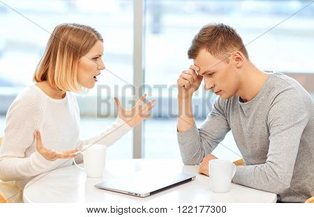 Petty disagreement. Cheerless emotional girl sitting at the table with boy and drinking coffee while quarreling