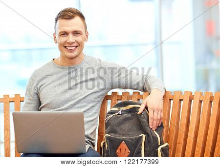 Have a great day. Cheerful handsome student sitting on the bench and smiling while working on the laptop