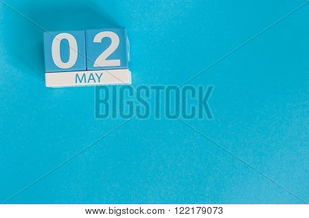 May 2nd. Image of may 2 wooden color calendar on blue background.  Spring day, empty space for text.