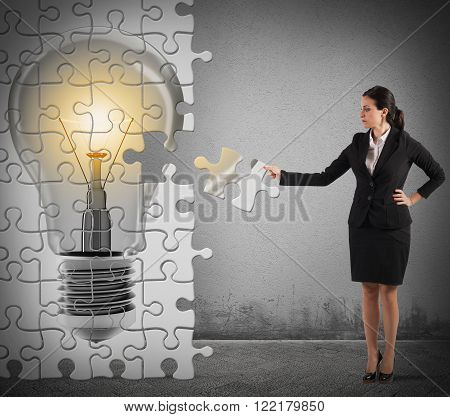Woman builds a puzzle with light bulb