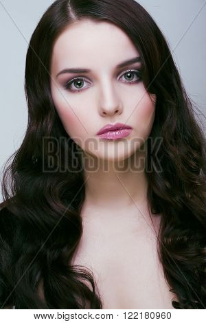 pretty young brunette woman with hair style like cute doll hairstyle waves, glamorous makeup close up