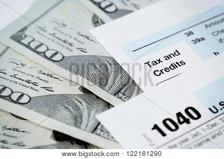 1040 Individual Income Tax Return Form with one hundred dollar bills on white background, close up