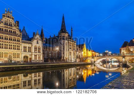 Picturesque medieval building and St Michael's Bridge on the quay Graslei in Leie river at Ghent town at evening, Belgium